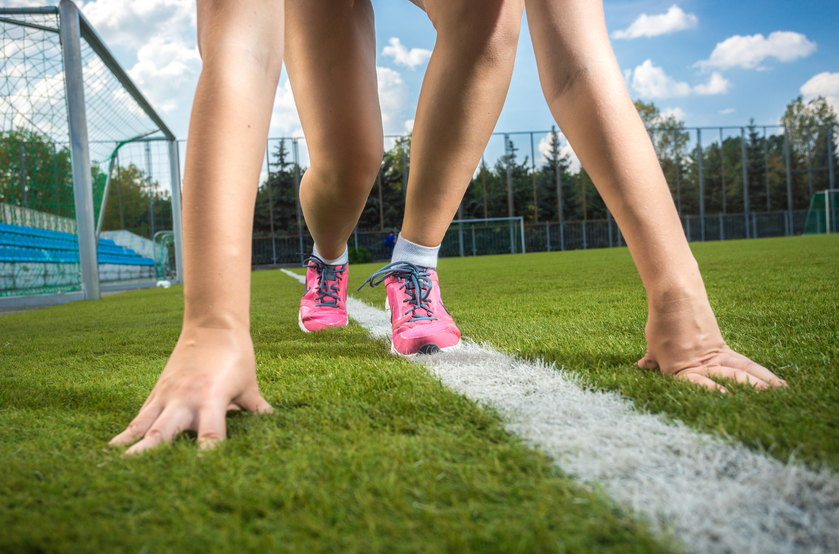 Closeup shot of slim sporty woman getting ready to run on grass track